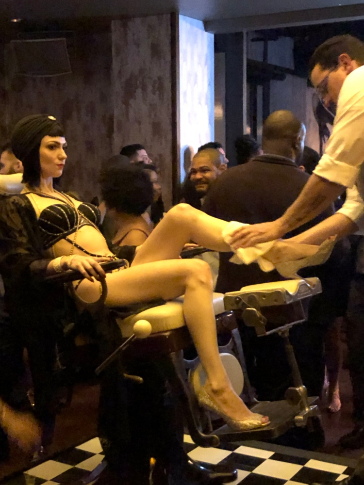 A flapper in black and pearls sits in a barber's chair in the middle of a club dance floor as a 1920s-styled barber shaves her legs.